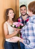 52043549-senior-woman-meeting-smiling-young-family-flowers-at-the-door
